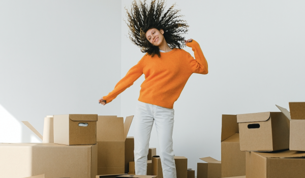 happy girl dancing amongst moving boxes