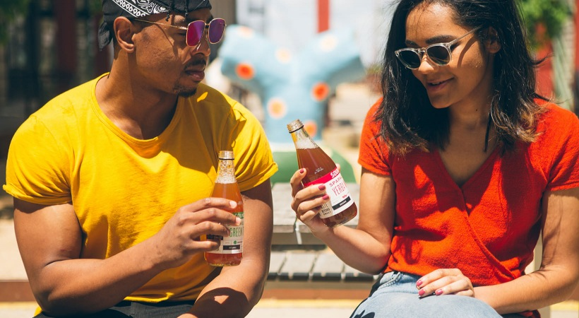 guy and girl sit out in the neighborhood and drink sparkling water