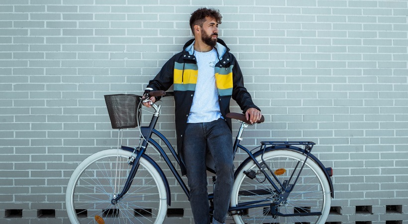 man in jacket stands in front of his bicycle in front of tiled wall